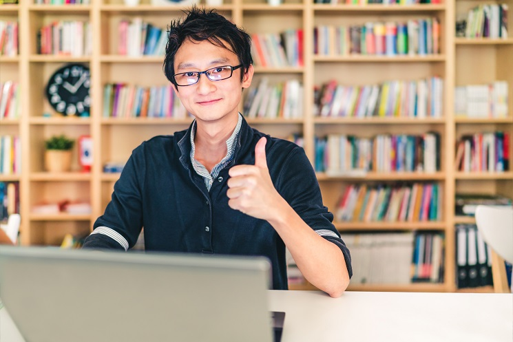 Asian man with laptop, thumbs up, at home office, library