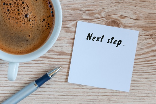 Next Steps inscription written in notepad near morning coffee cup