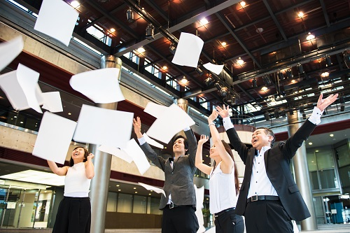 A goup of business people throwing away documents.
