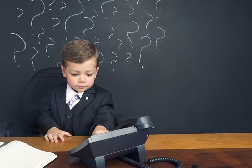 Uncertainty concept. Young boy sitting behind a desk