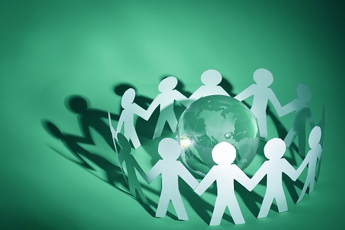business background.group of paper men standing around the glass globe