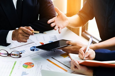 Business people using pen, tablet, notebook are planning a marketing plan to improve the quality of their sales in the future.